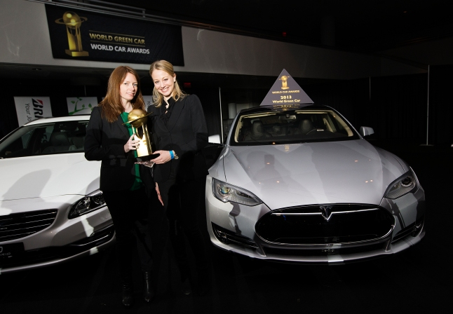 Tesla communications manager Katrina Schira, left, and vice-president of communications Sarah Meron, right, pose for a photo with the Tesla Model S after it has been named World Green Car of theYear at a press conference during the New York International Auto Show on Thursday, March 28, 2013. (Photo By: Michelle Siu for the World Car Awards)
