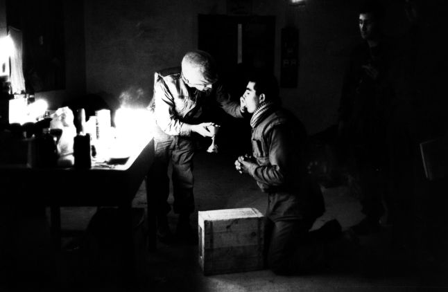 Marine chaplain Eli Tavesian giving communion to marine Louis A Loya, at Forward Command Post in Hue, Vietnam.    (Photo by Express Newspapers/Getty Images)