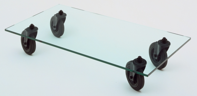 Designing Modern Women 1890–1990: Gae Aulenti (Italian, 1930–2012). Table with Wheels (model 2652). 1980. Glass, metal and rubber, h. 11 1/4 x w. 27 1/2 x l. 54 5/8″ (h. 28.6 x w. 69.9 x l. 138.7 cm). Mfr.: Fontana Arte, Italy. The Museum of Modern Art, New York. Gift of Donn Golden. © 2013 Sergio Asti