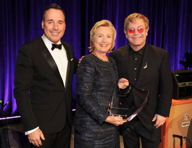 David Furnish, Hillary Rodham Clinton and Elton John pose on stage at the Elton John AIDS Foundation's 12th Annual An Enduring Vision Benefit at Cipriani Wall Street on October 15, 2013 in New York City.