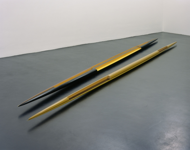 "Isa Genzken Rot-gelb-schwarzes Doppelellipsoid 'Zwilling' (Red-Yellow-Black Double Ellipsoid ""Twin""), 1982 Lacquered wood, two parts Overall: 9 7/16 x 8 1/16 x 473 1/4″ (24 x 33.5 x 1202.1 cm) Part one: 5 1/8 x 8 1/16 x 236 1/4″ (13 x 20.5 x 600 cm) Part two: 4 5/16 x 5 1/2 x 237″ (11 x 14 x 602 cm) Collection of the artist Courtesy the artist and Galerie Buchholz, Cologne/Berlin © Isa Genzken"