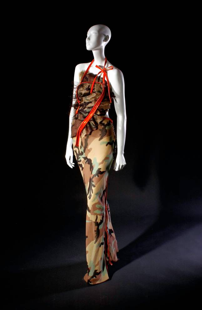 Christian Dior (John Galliano), evening dress, camouflage print silk, spring 2001, France, museum purchase (Camouflage evening dress; long asymmetrical sheath in khaki, black and green camouflage print silk; taffeta halter bodice with self ruffle and dotted net overlay, long skirt in bias cut crepe de chine; large orange plastic zippers for strap, closures and trim, with logo zipper pull)
