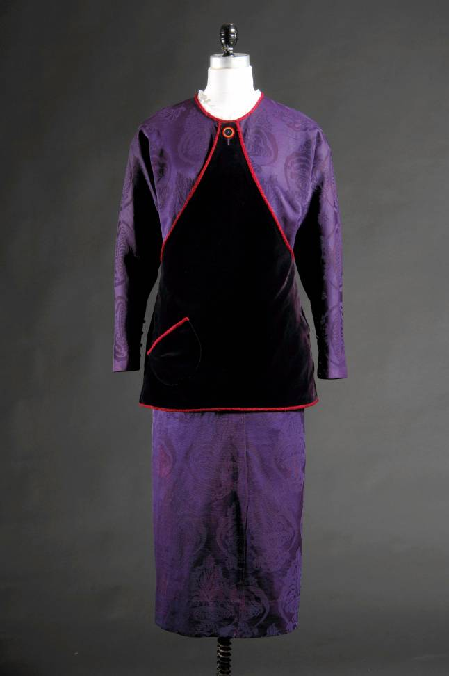 Paul Poiret, dress, purple silk damask with cotton velvet and fuchsia silk cord, 1912, France, museum purchase (Melodie afternoon dress in purple silk damask with triangular purple velvet knee length tunic attached at CF and CB neck and rounded patch pocket at R hip, contrasting fuchsia silk cord trim outlining tunic, neckline and pocket: round neckline with pleated white ruffle (not original to dress); round red, blue, tan Bakelite (?) button detail at CF neck; tapered full length sleeve cut in one with bodice; self covered buttons at cuff; tunic has hook & eye closure at L side seam; hook & eye closure at CB; straight silhouette; ankle length)