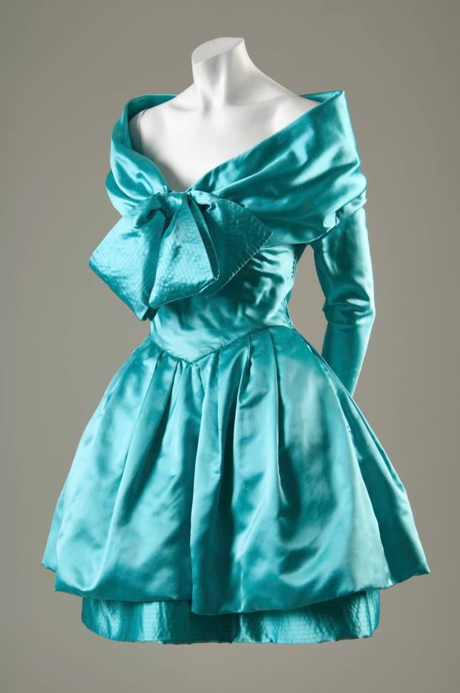 Christian Lacroix, evening dress, turquoise silk satin, circa 1988, gift of Mrs. Martin D. Gruss (Turquoise satin couture evening dress with oversized topstitched bow at CF neckline and pouf skirt: portrait style neckline; narrow full length sleeve; fitted bodice; corseted inner-bodice; full pouf skirt and slightly longer underskirt with decorative topstitching along hem; zipper closure at L side bodice; above knee length)