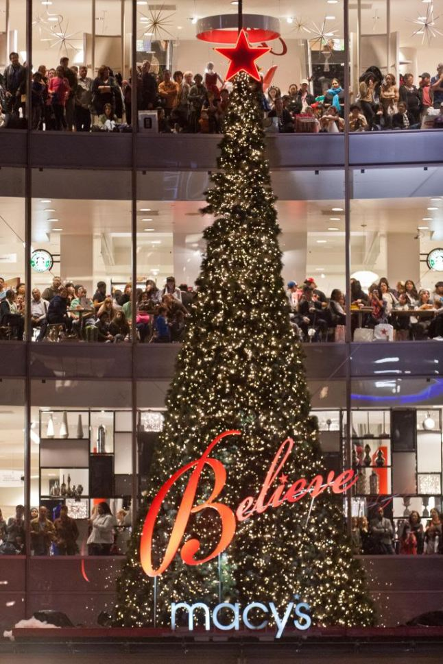 Holiday shoppers peer out of Macy's windows for the Great Tree Lighting in Union Square.