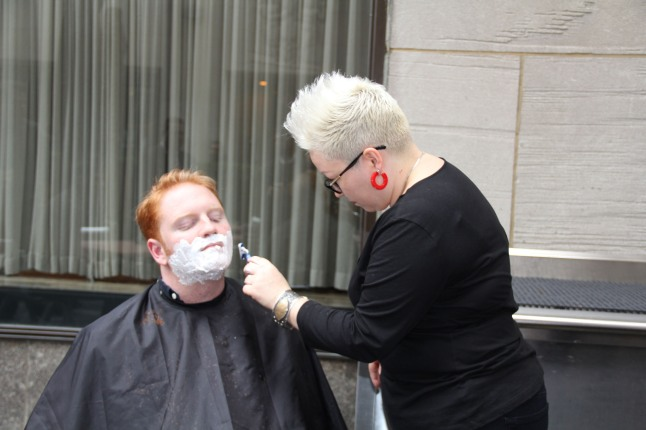 Celebrity stylist Carrie Butterworth gives Peter Hourihan a clean shave at Del Frisco's Grille in New York to start Movember.  (PRNewsFoto/Del Frisco's Grille)