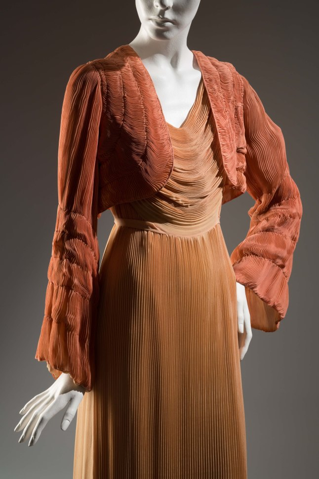 Dusty apricot silk chiffon evening dress; front of dress bodice is cowl draped with pleated chiffon used horizontally; pleats are caught at waist seam draping up either side and caught into piped armhole; panel of pleats hang from drape to floor at center front; plain underarm panel of chiffon on either side; pleated panel of chiffon hangs from wide piped neck to back dipping hem; 3/4 inch self sash from front ties around waist to back bow. Dusty apricot silk chiffon bolero entirely pleated; pleats swirl from horizontal in front to vertical at back and are held by rows of stitching; flaring sleeves vertically pleated with five rows of stay stitching from elbow to cuffs; lined in sheer silk. Apricot silk crepe slip with fitted bust yoke edged at top with nude marquisette; narrow marquisette straps; long fitted darts on either side front; elasticized panel across back at waist; slit on either side at hem has scallops which continue around hem; scalloped chiffon addition 2.5 inches wide around crepe hem; zipper closing at left side. HélèneYrande, Negligee ensemble, Coral and peach pleated, Silk chiffon, 1932, France                                                                                                      The Museum at FIT, 75.69.9, Gift of Sophie Gimbel