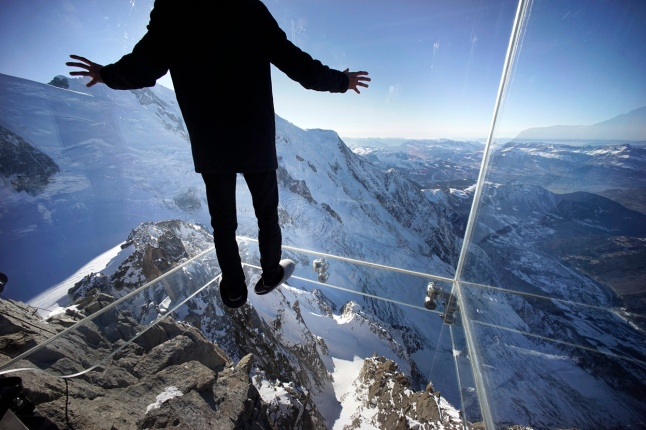 "A journalist, wearing slippers to protect the glass floor, stands in the ""Step into the Void"" installation during a press visit at the Aiguille du Midi mountain peak above Chamonix, in the French Alps, on December 17, 2013. The Chamonix Skywalk is a five-sided glass structure installed on the top terrace of the Aiguille du Midi (3842m), with a 1,000 meter drop below, where visitors can step out from the terrace, giving the visitors the impression of standing in the void. The glass room will open to the public on December 21, 2013. (Reuters/Robert Pratta)"