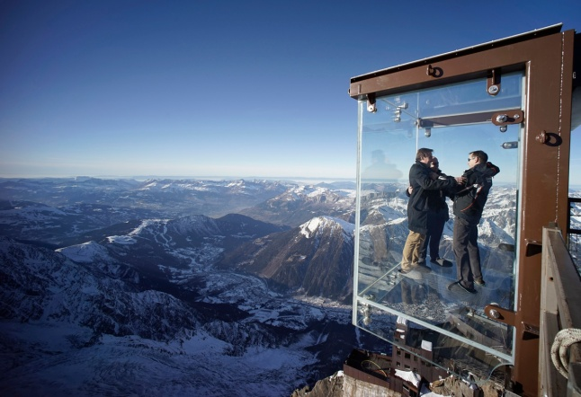 Journalists and employees, wearing slippers to protect the glass floor, stand in the Chamnonix Skywalk atop Aiguille du Midi, on December 17, 2013. (Reuters/Robert Pratta)