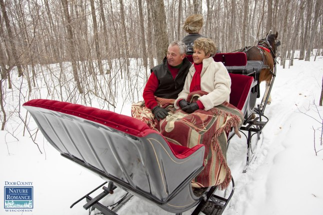 A couple enjoys a romantic horse-drawn sleigh ride through the woods in Door County, Wisconsin during the annual Nature of Romance promotion. Photo courtesy Mike Roemer/DoorCounty.com.