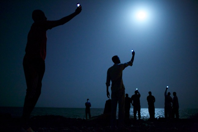 Impoverished African migrants crowd the night shore of Djibouti city, trying to capture inexpensive cell signals from neighboring Somalia—a tenuous link to relatives abroad. For more than 60,000 years our species has been relying on such intimate social connections to spread across the Earth. Credit: John Stanmeyer, Freelance
