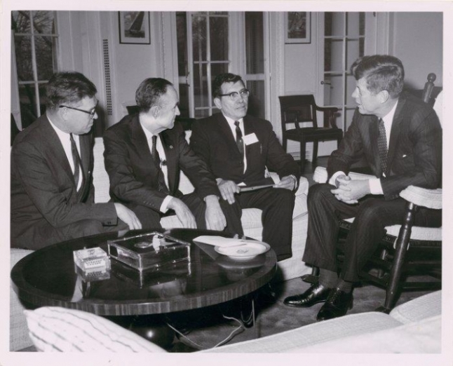 President John F. Kennedy meeting with National Congress of American Indians (NCAI) president Walter Wetzel, Senator Lee Metcalf, and Senator Mike Mansfield, 1963. Photo probably by Robert L. Knudsen. (P34169)
