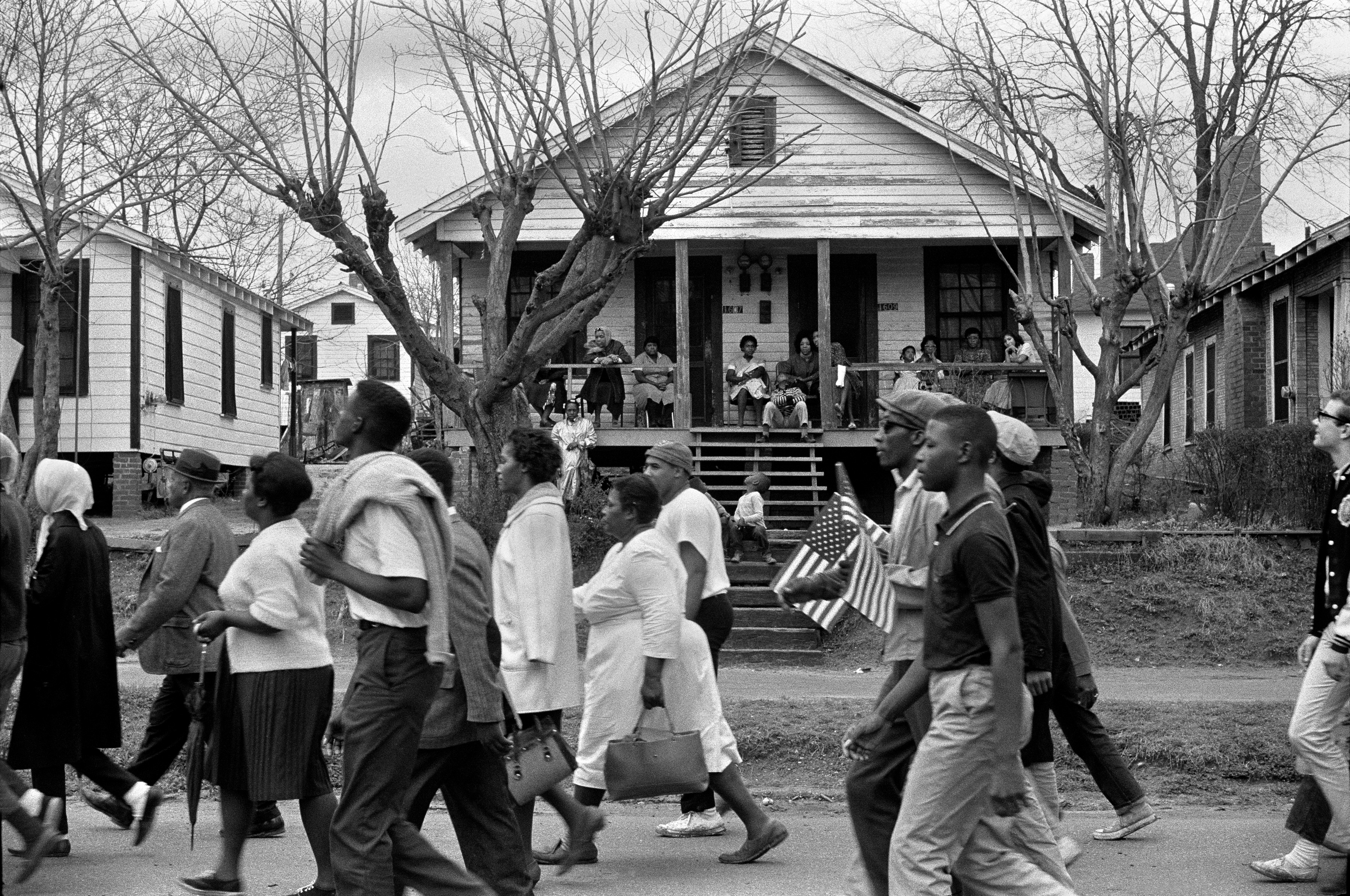 Stephen Somerstein, Marchers on the way to Montgomery as families watch from their porches, 1965. Courtesy of the photographer