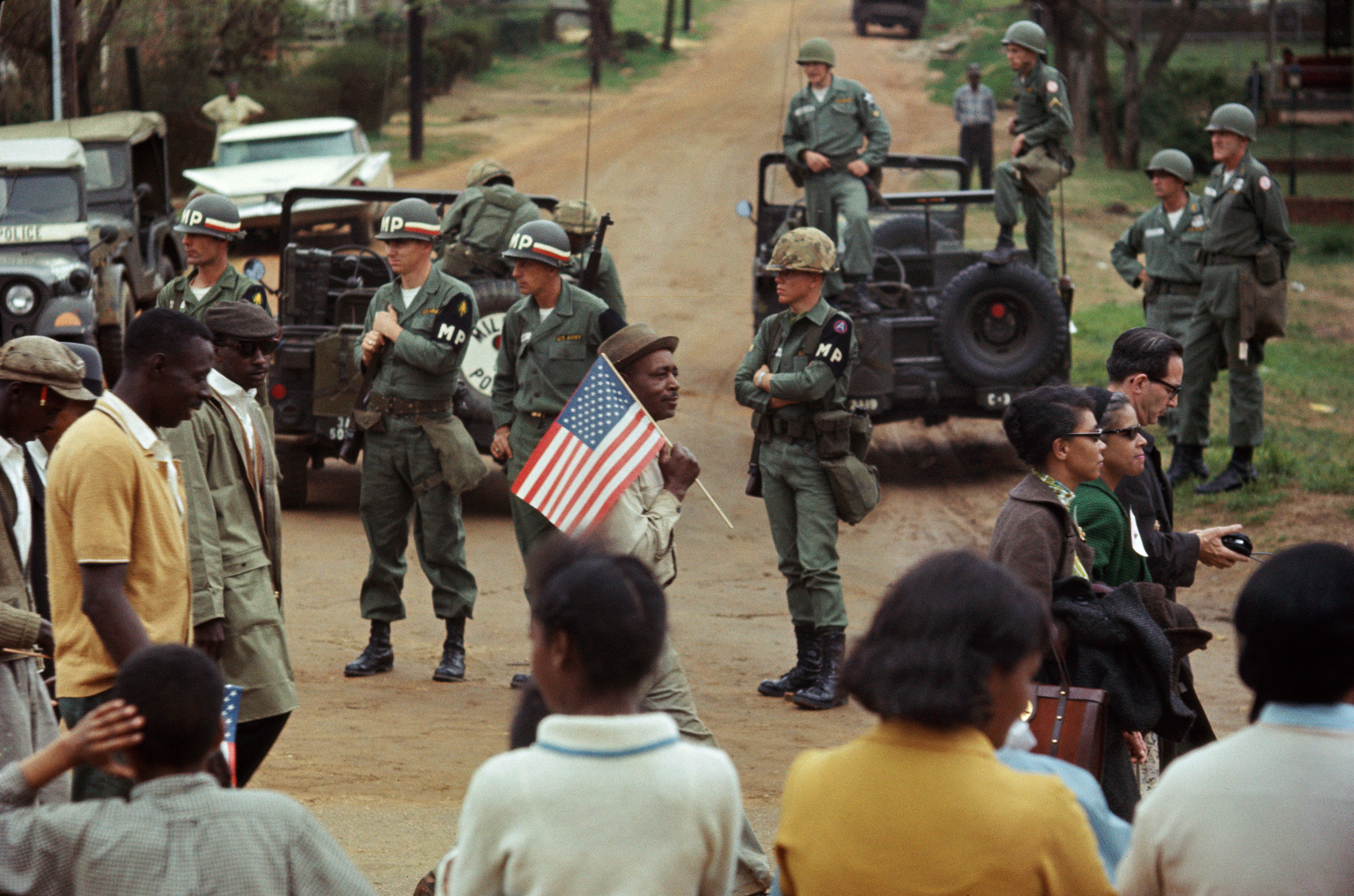 Stephen Somerstein, Man with American flag and marchers walking past federal troops guarding crossroads, 1965. Courtesy of the photographer