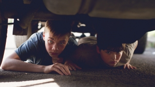 Jack (Charlie Plummer) and Ben (Cory Nichols) hide under a car to avoid Shane, the vicious local bully. Photographer: Brandon Roots