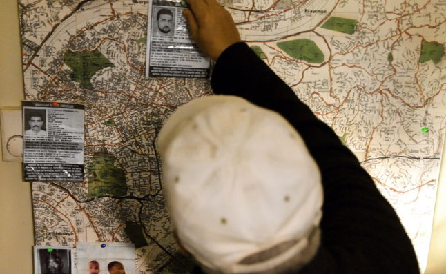 Image of informant pinning photos to a map: Shariff arranges photographs, depicting the FBI?s most wanted terrorists and other persons of interest, atop a map of Pittsburgh. (photographer credit: Lyric R. Cabral)