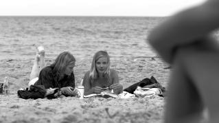 Ramona (Gro Swantje Kohlhof, links) blickt in die Zeitschrift, während Jennie (Saskia Rosendahl, rechts) Stefans Blicke auf sich zieht und mit ihm flirtet.
