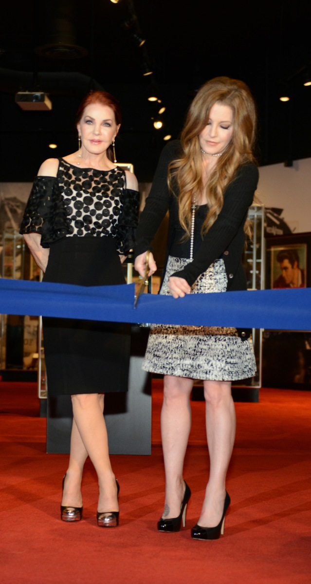 """Priscilla Presley and Lisa Marie Presley preside over the formal blue suede ribbon cutting ceremony, officially opening """"Graceland Presents: Elvis"""" on April 23, 2015"""
