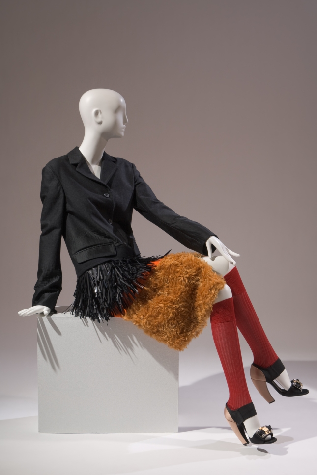 Prada , Ensemble , Fall 2007, Milan, Gift of Prada, 2007.20.1 Coat with black textured wool blazer fringed with plastic strips, stitched to orange fleece skirt with rust pile hem band; red silk ribknit toeless stockings; black satin shoes with hardware buckle, high curved heel and back covered in taupe satin