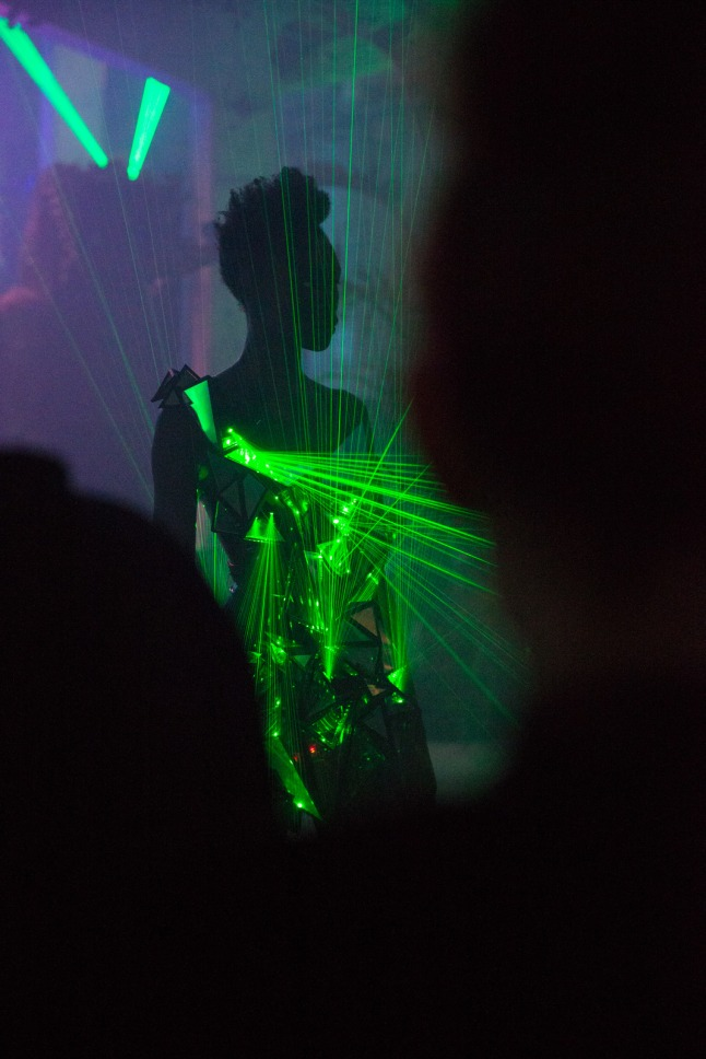 Partygoers wore bespoke outfits made with fabrics embedded with lasers and mirrors which were wirelessly controlled from a central server, so they could choreograph and synchronize the lasers. Wearable technology allowed guests to be integral part of the artistic experience, breaking free of their expectations of a night out.