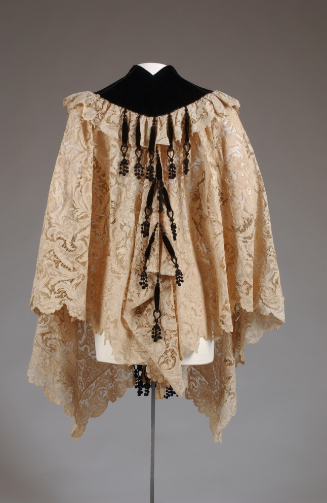 The House of Worth, Cape, Circa 1890. Paris. Gift of the Estate of Elizabeth Arden. 69.160.9 Hip-length cape in cream lace with wide neckline border of black silk velvet; trimmed with black silk chenille bobble tassels