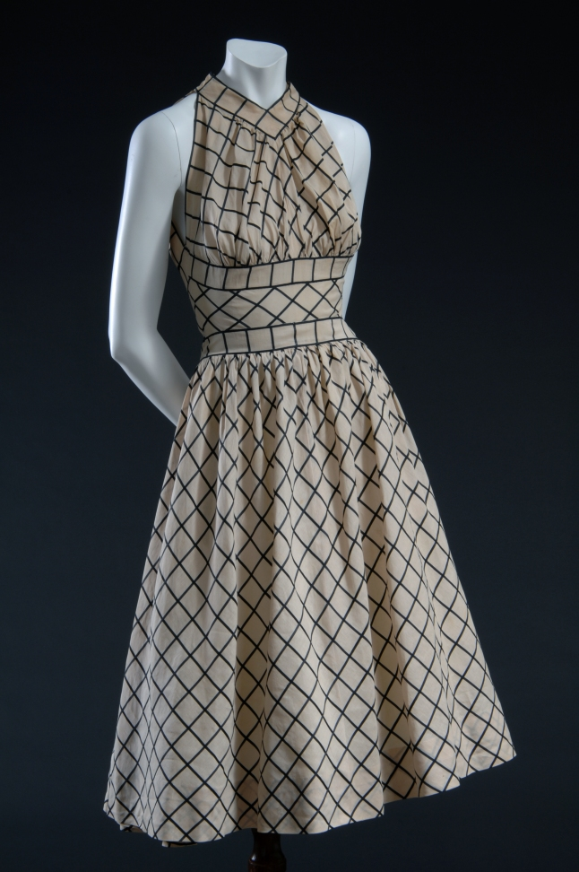 Claire McCardell, Dress, 1954, New York . Gift of Sally Kirkland. 76.33.34_20080425_01 Sleeveless dress in beige muslin with black windowpane check; fitted midriff panel; calf-length flared skirt; wide wrap & tie sash