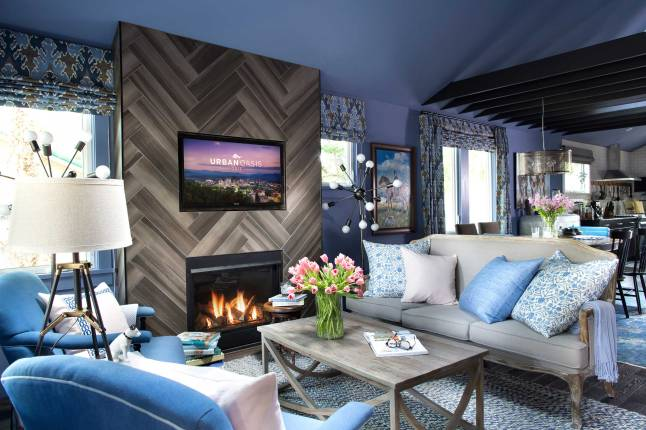 Inside the front door of the HGTV Urban Oasis, the dramatic blue-gray walls and comfortable seating are centered around a ceiling-high fireplace set in a beautiful herringbone-patterned tile.