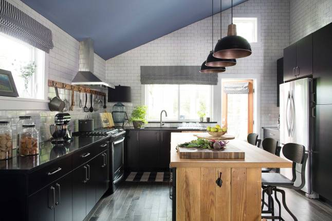 The black kitchen cabinetry of the HGTV Urban Oasis 2015 pops against the white floor-to-ceiling subway tile, while the center island fashioned from reclaimed wood gives the space a nice warmth.