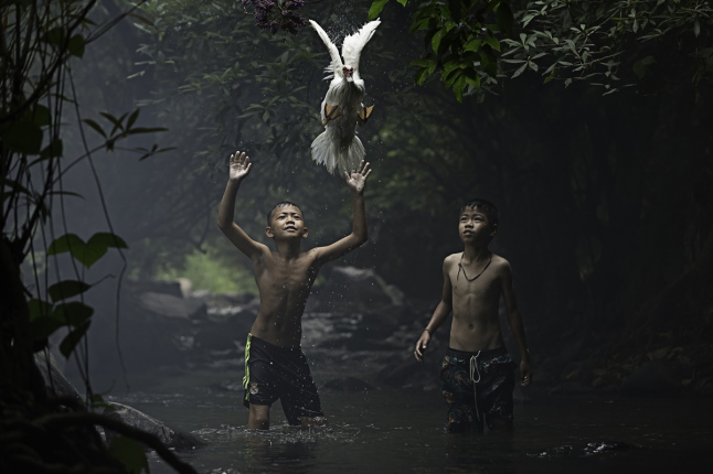 Two boys are trying to catch a duck near a waterfall. # © Sarah Wouters / National Geographic Traveler Photo Contest