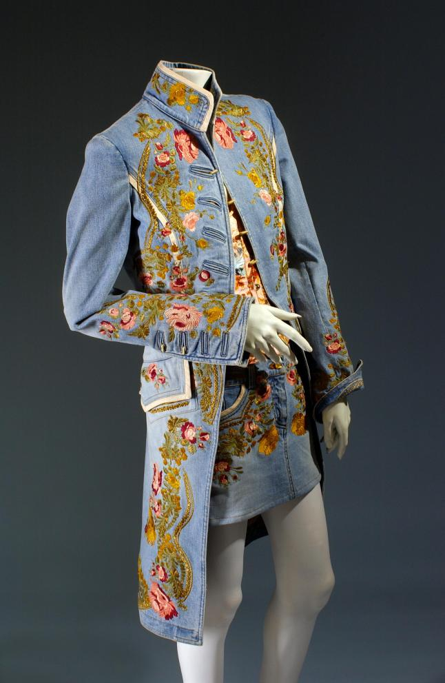 18th century/1960s-inspired ensemble with light blue denim redingote and micro mini skirt embroidered with large floral border design, silk crepe de chine camisole and boned corset in contrasting pale and deep pink floral prints. Roberto Cavalli, ensemble, embroidered denim, spring 2003, Italy, gift of Roberto Cavalli. Photograph courtesy of The Museum at FIT.