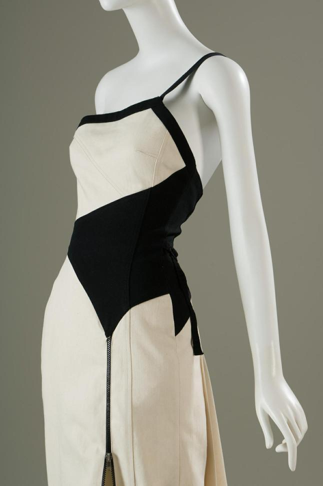 White and black organic tunisian denim one shoulder gown with black denim trim and shoulder strap, pieced black panel at waist, front zippered slit at front L, and pleated white denim deatchable train attached at back . Edun, dress, white and black denim, 2007, USA, gift of Edun. Photograph courtesy of The Museum at FIT.