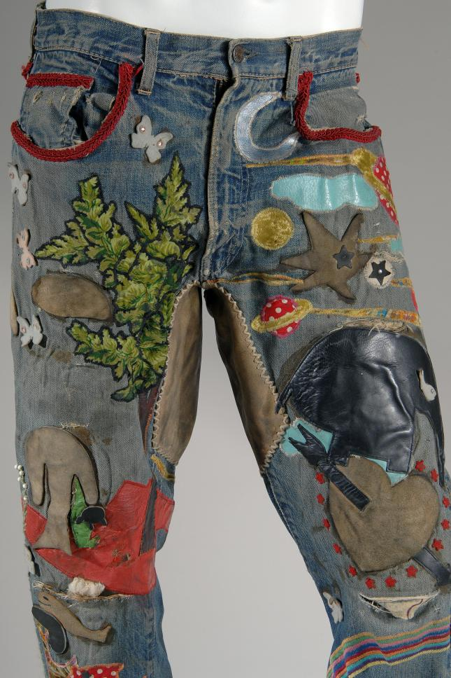 Embellished men's jeans; blue denim 5-pocket jeans with multicolor overall applique, beadwork, hand and machine embroidery, incorporating leather, vinyl, contrast fabric, rhinestones and cord. Levi Strauss & Co., jeans, embroidered denim, circa 1969, USA, gift of Jay Good. Photograph courtesy of The Museum at FIT.