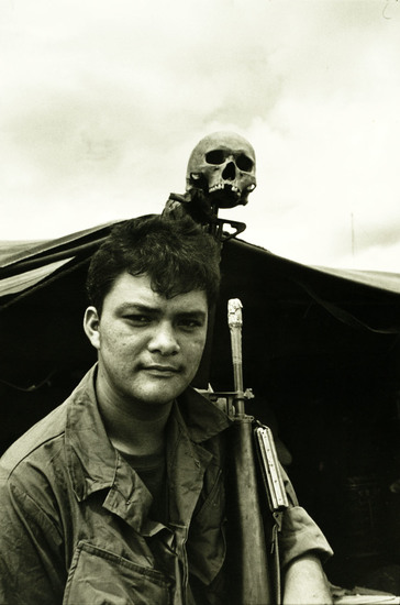 "Hoochmate, 1968. An infantryman with the 1st Battalion, 12th Infantry, 2nd Brigade, U.S. Army 4th Infantry Division displays above his tent a skull that he found on patrol near Camp Warrior in Pleiku Province. Photo by Specialist 5 Richard A. ""Dick"" Durrance, U.S. Army."