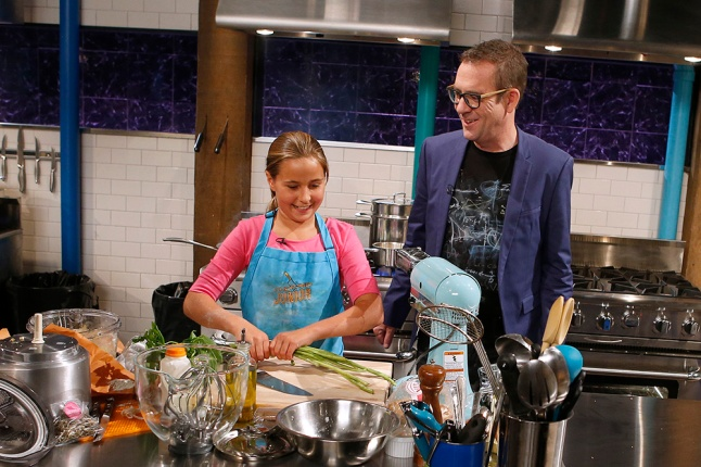 Host Ted Allen checks in on junior chef Grace LaFountain as she cooks with lamb loin chops, mini pepperoni pizzas, Chinese long beans and orzo during round 2 as seen on Food Network's Chopped Junior, Season 1.