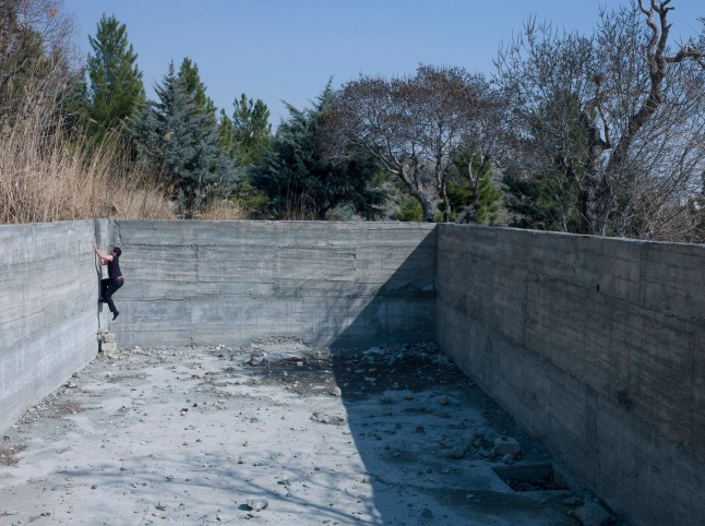 Thomas Erben Gallery, Newsha Tavakolian. Mahud, climbing the wall of the abandoned empty swimming pool, which is the only quiet place he can find to practice singing, 2014. Courtesy the artist and the gallery