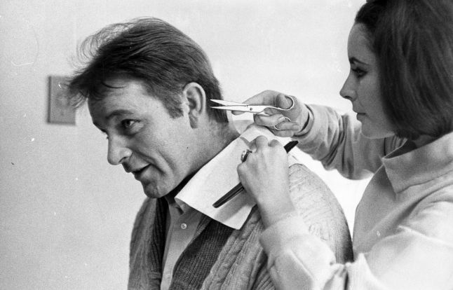 6th March 1964:  Elizabeth Taylor gives her future husband Richard Burton (1925-1984) a cursory haircut.  (Photo by William Lovelace/Express/Getty Images)
