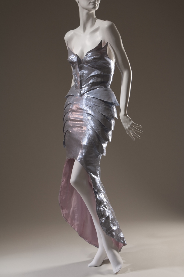 """Thierry Mugler, ensemble, circa 1987, France. Evening set; lilac/silver metallic form fitting winged bustier and skirt with fishtail train in polyester and lurex blend. The Museum at FIT, 2011.13.1, photograph © The Museum at FIT (illustrating """"The Little Mermaid"""")"""