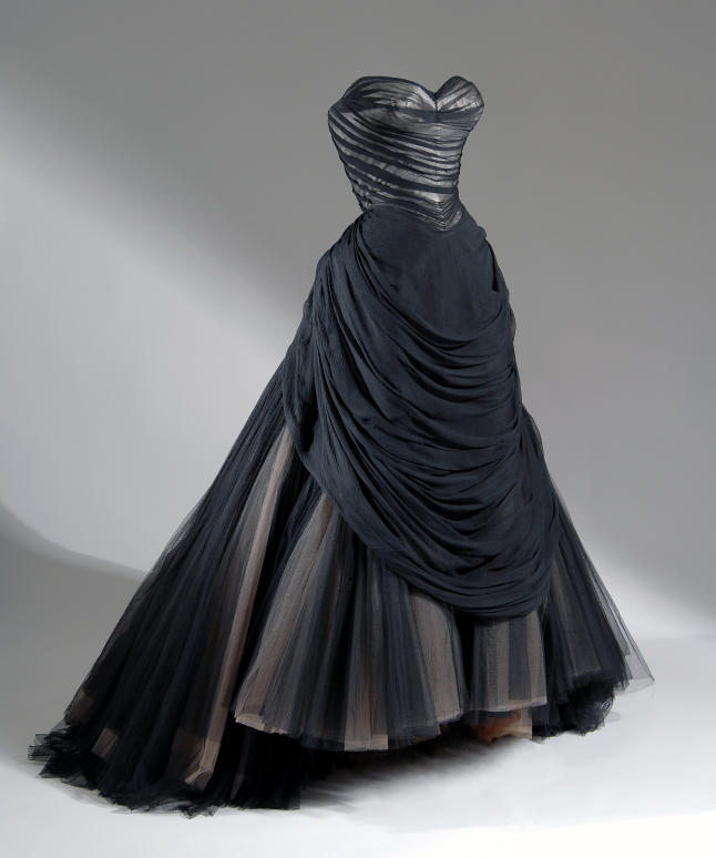 """The Bustle or Swan ballgown: strapless boned bodice in black chiffon draped in folds over white satin; floor-length sweeping trained full skirt with layers of black, beige and brown net gathered into back bustle roll and forming wide polonaise or apron front swag; stiffened understructure. Charles James, Swan evening dress, 1954-1955, USA. The Museum at FIT, 91.241.136, photograph © The Museum at FIT (illustrating """"The Swan Maidens"""")"""
