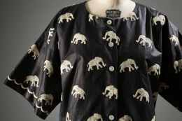 Carolyn Schnurer, top, 1952. Top of black polished cotton with overall white schifflie embroidered elephants; open round neckline; drop shoulder; short sleeve straight line; 6 button center front closing. Collection of The Museum at FIT. © The Museum at FIT.