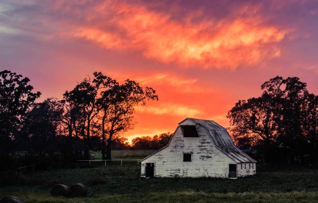 Sunset fades behind a long standing barn along AR 112 on the outskirts of Bentonville, Arkansas © Chris Works - 500px