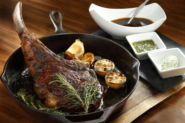 a-54-ounce-mishima-prime-tomahawk-ribeye-steak-is-cooked-to-perfection-and-served-alongside-chef-morimotos-signature-sweet-onion-and-garlic-jus
