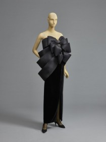 Woman's Evening Ensemble: Top and Skirt, 1989, designed by Pierre Cardin. Top: Silk faille, rayon stretch net lace, rhinestones; Skirt: Cellulose acetate velvet. Philadelphia Museum of Art: Gift of Mrs. Jack M. Friedland (Annette Y. Friedland). a) Black net tube top with 3 oversized black silk faille bows at center front with rhinestones; black silk faille bands encircle bust and wrap over left shoulder b) Black velvet full-length skirt with left side slit.