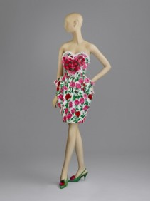 Woman's Two-Piece Dress: Top and Skirt, Spring/Summer 1988, designed by Christian Lacroix. Pink, red and green printed white cotton brocade; white cotton and acrylic ribbon; pink, red and green synthetic plain weave. 125th Anniversary Acquisition. Philadelphia Museum of Art: Gift of Kathleen P. Field. Pink, red, green and white cotton brocade strapless bustier top, sweetheart neckline and peplum at waist, pink and red fabric roses in a heart shape at bust b) Matching short tulip-shape pleated skirt